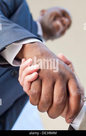Afrikanische amerikanische Geschäftsmann oder Mann Händeschütteln mit einem kaukasischen Kollegen machen ein Geschäft - Stockfoto