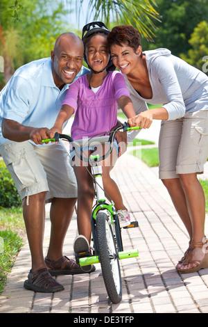 Eine junge afroamerikanische Familie mit Mädchen reiten ihr Fahrrad und ihre glücklichen begeisterten Eltern ermutigen - Stockfoto