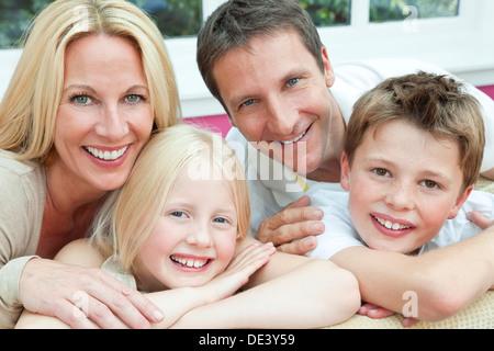 Eine attraktive, Familienglück von Mutter, Vater, Sohn und Tochter sitzen auf einem Sofa zu Hause Spaß - Stockfoto