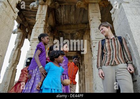 Ein paar indische Mädchen an einen deutschen mittleren Alters weibliche Touristen in großer Ganesha-Tempel in Hampi, - Stockfoto