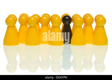 Eine schwarze Figur, umgeben von gelben Figuren, symbolisches Bild für das schwarze Schaf in der Gruppe - Stockfoto