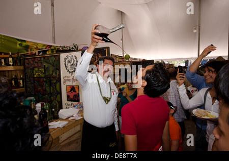 Man gießt Wein in einen anderen Mann Mund beim nationalen Festival von Käse und Wein in Tequisquiapan, Queretero - Stockfoto