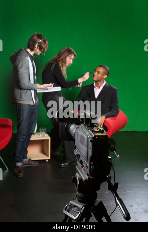 Selektiven Fokus auf eine Studio-Fernsehkamera mit Floor-Manager, Visagistin und Moderatorin im Hintergrund unscharf. - Stockfoto
