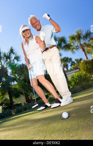 Glücklicher senior Mann Frau Paar zusammen Golf spielen, setzen auf grün, den Ball in das Loch, einem erfolgreichen - Stockfoto