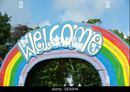 Das heitere Wort willkommen auf einem Regenbogen Schild über einem hölzernen Bogen am Camp Bestival Musik Festival - Stockfoto