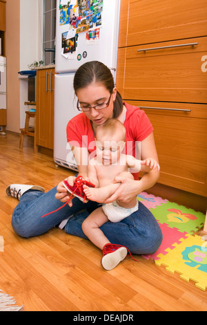 Mutter, 28 Jahre, mit Baby, 1 Jahr, Schuhe anziehen - Stockfoto