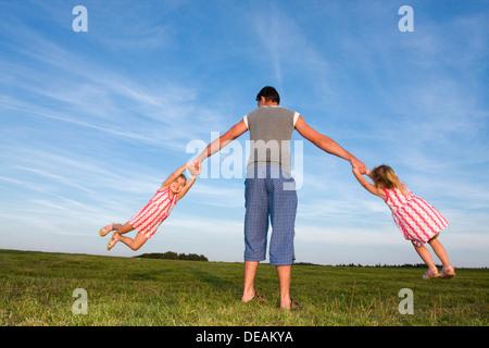 Zwillingsmädchen, 3 Jahre, spielen mit ihrem Vater, 29 Jahre, im freien - Stockfoto