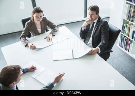 Drei Geschäftsleute sitzen um einen Tisch und ein Business-Meeting, hoher Winkel anzeigen - Stockfoto