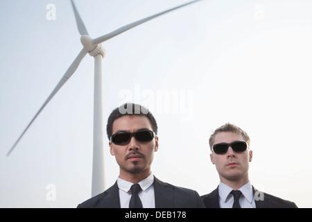 Porträt von zwei schweren Jungunternehmer in Sonnenbrillen stehen durch eine Windenergieanlage - Stockfoto
