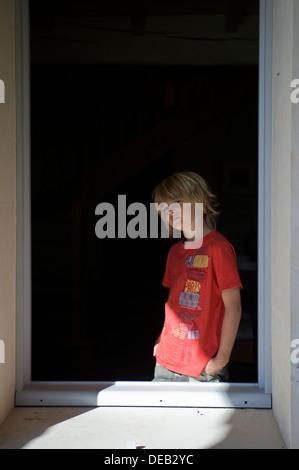 Eine stimmungsvolle Blondschopf schaut aus dem Fenster - Stockfoto