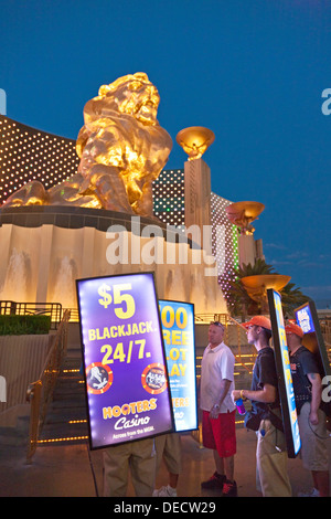 Tragbare Lichtwerbung Bildschirme neben Leo Löwe Bronze Statue im MGM Grand, Las Vegas, Nevada, USA in der Abenddämmerung. - Stockfoto
