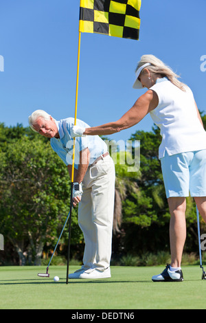 Glücklich senior Mann und Frau Paar zusammen spielen Golf auf einem grünen Zusammenstellung - Stockfoto