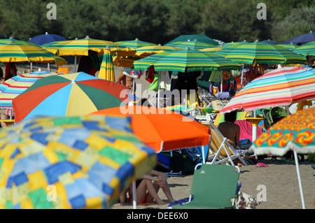viele Sonnenschirme gestapelt an den Ufern des Meeres auf dem überfüllten Strand - Stockfoto