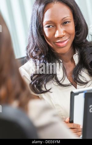 Junge schwarze afrikanische Amerikanerin oder Geschäftsfrau in intelligente Business-Anzug mit einem Tablet-Computer - Stockfoto