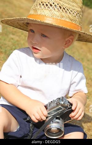 ein niedliches Baby-junge trägt einen Strohhut sitzt draußen spielen mit einem Vintage-Kamera - Stockfoto