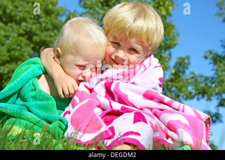 Zwei Brüder, ein Baby und ein kleines Kind, umarmen einander außerhalb an einem sonnigen Sommertag in ein Badetuch. - Stockfoto
