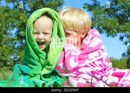 Zwei glückliche junge Kinder; ein kleiner Junge und seinem kleinen Bruder, lachen und Kuscheln unter hellen bunten - Stockfoto