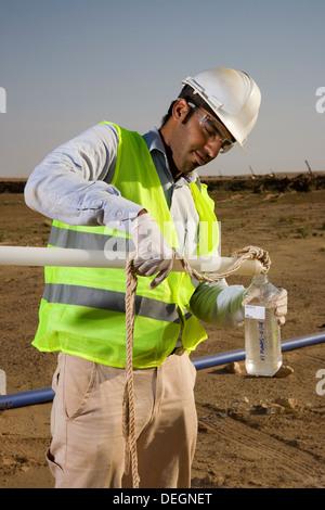 Nehmen Wasser, die Proben aus trug Loch, um zu testen, Qualität auf industriellen Goldabbau Komplex, Mauretanien, - Stockfoto