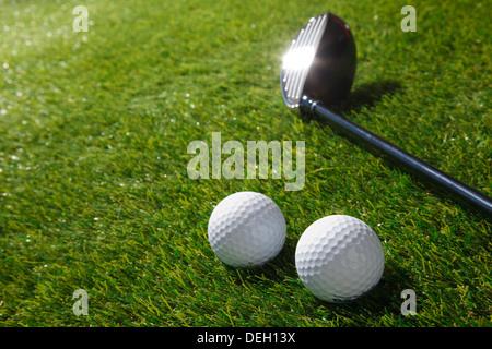 Golfbälle und Club auf Rasen - Stockfoto