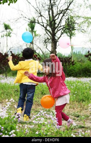 Ostasiatische Kinder draußen spielen - Stockfoto