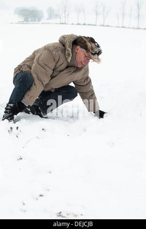 Senior woman mit verletzten Bein auf Schnee. - Stockfoto