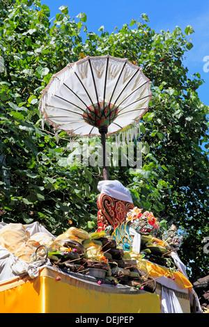 Stapel der Tempel Angebote auf ein Heiligtum mit einem Drachen Statue und Regenschirm. Sanur, Bali, Indonesien
