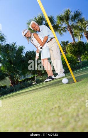 Glücklicher senior Mann und Frau Paar zusammen Golf spielen und setzen auf eine grüne, der Mann der Frau lehrt wie - Stockfoto