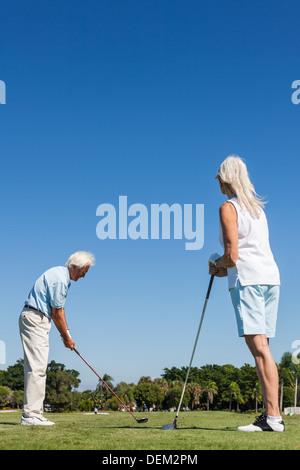 Glücklicher senior Mann und Frau Paar zusammen Golf spielen auf einem Golfplatz in der Nähe von einem See sind sie - Stockfoto