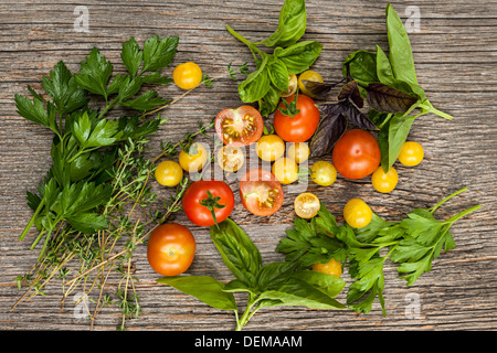 Frischen bunten Tomaten und Kräutern auf rustikalen hölzernen Hintergrund von oben - Stockfoto