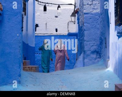 Zwei Frauen tragen traditionelle Kleidung zu Fuß in einer Straße mit blau gestrichenen Wänden in Chefchaouen, Marokko - Stockfoto