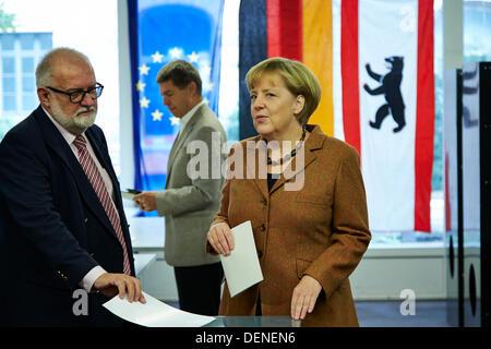 Berlin, Deutschland. 22. September 2013. Angela Merkel (CDU), Bundeskanzlerin, mit ihrem Ehemann warf ihre Stimmzettel - Stockfoto