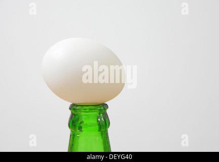 Ei auf Bierflasche ausgeglichen - Stockfoto