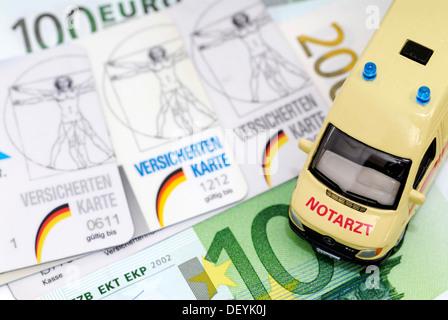 Krankenversicherungskarten und Miniatur-Ambulanz, symbolisches Bild für die finanziellen Schwierigkeiten der Krankenkassen - Stockfoto