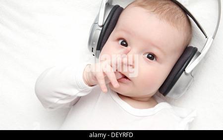 Baby Boy mit Kopfhörer liegt auf Rücken - Stockfoto