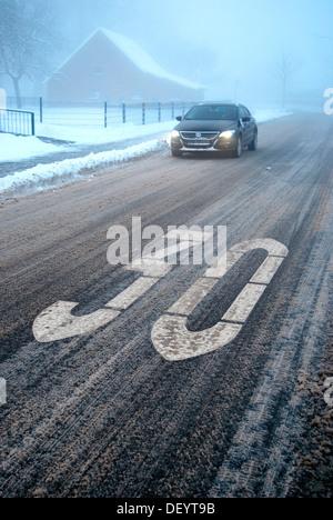 Rutschgefahr in einer beruhigten Bereich, Schneematsch auf einer winterlichen Straße mit Nebel, Borken, Gemen Bezirk, - Stockfoto