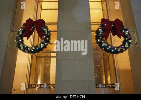 Weihnachtskränze als Dekoration hängen oberhalb der Türen von einem Gebäude an der Fifth Avenue, Manhattan, New - Stockfoto