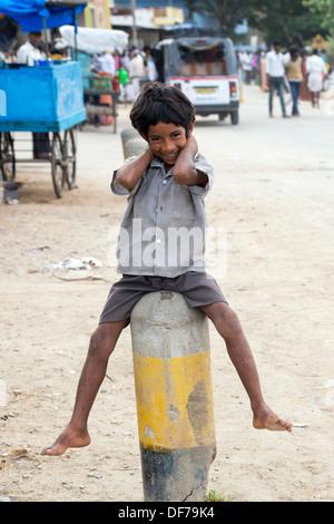 Glücklich lächelnde untere Kaste indischer Junge sitzt auf einem Post in einem indischen Straße. Andhra Pradesh, - Stockfoto