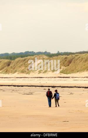 Ein paar Hände halten in der Liebe zu Fuß auf einer menschenleeren Strand von Whitby auf Anglesy mit Sanddünen in - Stockfoto