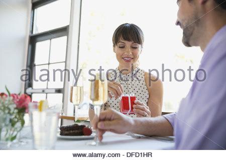 Frau Eröffnung Geschenk Mann während des Essens - Stockfoto