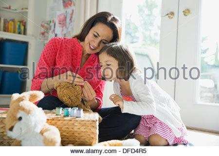 Neugierige Mädchen lernen, Faden Nadel - Stockfoto