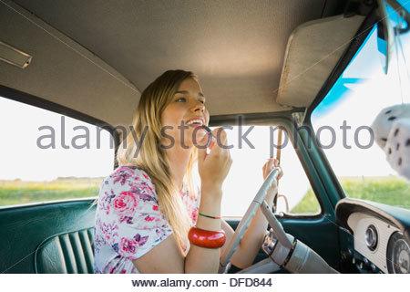 Schöne Frau Auftragen von Lippenstift in Pick-up-truck - Stockfoto