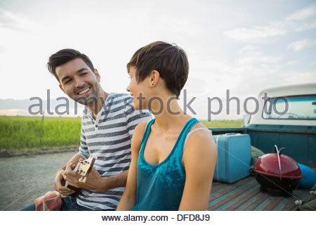 Junger Mann Gitarre spielen für Frau hinter Pick-up-truck - Stockfoto