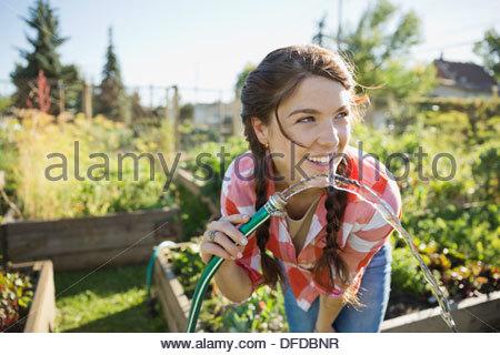 Frau Trinkwasser aus Gartenschlauch - Stockfoto