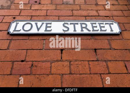 Liebe Straßenschild auf einer roten Backsteinmauer - Stockfoto