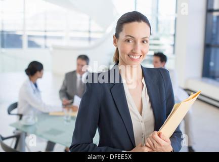Porträt von lächelnden Geschäftsfrau in Besprechung mit den Ärzten - Stockfoto