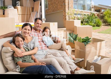 Porträt des Lächelns Familie sitzt auf dem Sofa in der Nähe von Möbelwagen in Einfahrt - Stockfoto
