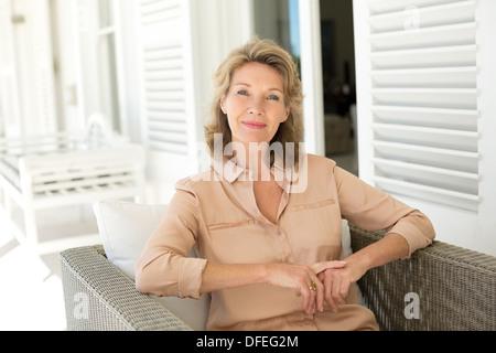 Porträt der lächelnde senior Frau sitzt auf Hof - Stockfoto
