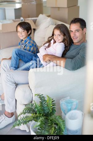 Vater und Kinder entspannend auf Sofa unter Kartons - Stockfoto