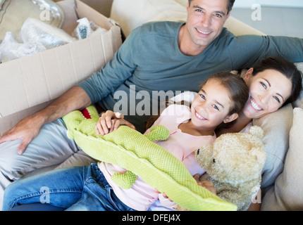 Porträt des Lächelns Familie mit ausgestopften Tieren auf sofa - Stockfoto