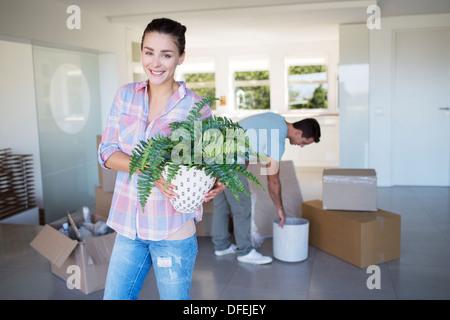 Porträt von lächelnden Frau mit Topfpflanze im neuen Haus - Stockfoto